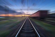 Gare ferroviaire avec des chariots de cargaison dans l'effet de tache floue de mouvement au sunse Photographie stock