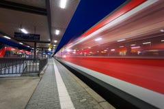 Gare ferroviaire moderne avec le train de voyageurs à grande vitesse sur la voie ferrée dans le mouvement la nuit Images stock