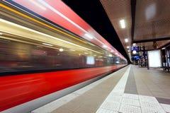 Gare ferroviaire moderne avec le train de voyageurs à grande vitesse sur la voie ferrée dans le mouvement la nuit Photo libre de droits
