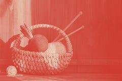 Garen met hyacint in mand met het kniting van stokken op oude houten achtergrond koraal Duotone stock afbeeldingen