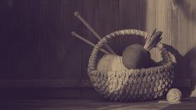Garen met hyacint in mand met het kniting van stokken op oude houten achtergrond wijnoogst Duotone stock afbeeldingen