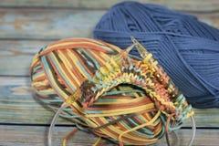 Garens in mand met haaknaalden in harmonische kleuren breien, die levering haken stock afbeelding