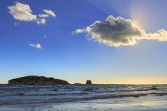 Gargano海岸:Portonuovo海滩,在波浪之间的维耶斯泰普利亚意大利小岛由光束横渡的云彩控制了 库存图片