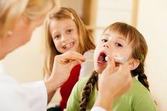 Garganta de exame do doutor do pediatra da menina Imagens de Stock Royalty Free