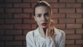 Garganta inflamada infeliz do sentimento da mulher e tossir no fundo da parede de tijolo video estoque