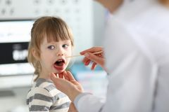 Garganta paciente de exame da crian?a do paediatrician f?mea com vara de madeira imagem de stock