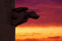 Gargoyle ενάντια σε έναν κόκκινο νεφελώδη ουρανό Σύμβολο Mytology και κενό διάστημα αντιγράφων Στοκ φωτογραφία με δικαίωμα ελεύθερης χρήσης