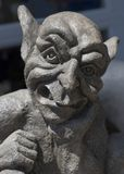 Gargoyle. A statue of a gargoyle shown from the shoulders up. He has his hand under his chin like he is thinking about something stock photo