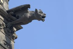 Gargoyle. A stone gargoyle juts out from a cathedral against a deep blue sky Stock Image