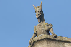 A Gargoyle against a blue sky. Stock Photos