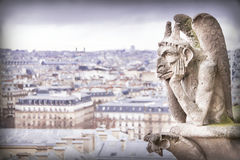 Gargoyle (chimera), stone demons, with Paris city on background. Royalty Free Stock Photography