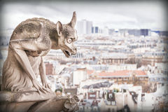Gargoyle (chimera), stone demons, with Paris city on background. Stock Photo