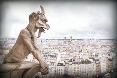 Gargoyle (chimera), stone demons, with Paris city on background. Royalty Free Stock Image