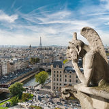 Gargoyle and city view from the roof of Notre Dame de Paris Stock Photos