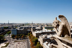 Gargoyle contemplating Paris. One of the Gargoyles of Notre Dame cathedral looking over Paris with Eiffel tower in the background Royalty Free Stock Image