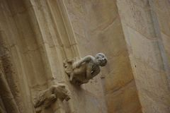 Gargoyle on the facade of a church. The sculpture representing a human figure with closed eyes and sad Stock Photography