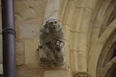 Gargoyle on the facade of a church. The sculpture representing a human figure with closed eyes and sad Royalty Free Stock Photos