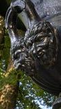 Gargoyle faces on cast iron urn stock photography
