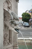Gargoyle in a fountain spitting water by mouth. Retail of gargoyle in a fountain spitting water by mouth Stock Images