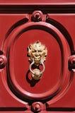 Gargoyle head door knocker. On red door in Mdina, Malta Stock Images