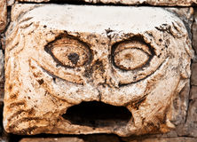 Gargoyle-like face on the stone Stock Photography