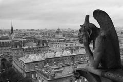 Gargoyle overlooking Paris. Gargoyle on Notre Dame overlooking Paris on a cloudy day Stock Photos