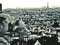 Gargoyle in Paris. A Gargoyle on Sacré- Coeur is looking out on Paris, Eiffel Tower in background Royalty Free Stock Photography