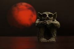 Gargoyle in red moonlight. Gargoyle figure on black with red moon Stock Image