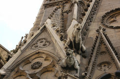 Gargoyles looking down from Notre Dame, Paris, France. Terrifying gargoyles on Notre Dame, built with a purpose to drain water off the roof and to protect the Royalty Free Stock Photo
