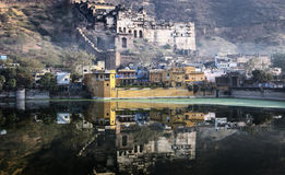 Garh Palace in Bundi,India. The Garh Palace is reflected in the lake by the city of Bundi. Vapor and fog bear witness to the early morning mood Royalty Free Stock Photos