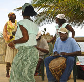 Garifuna Dancer and Musicians, Honduras. A dancer to Garifuna music moves her hips in a traditional circular style, as musicians play their drums and shakers stock photos