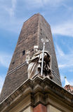 Garisenda tower and the statue in Bologna Royalty Free Stock Image