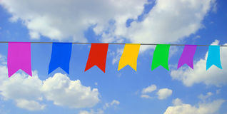 Garland. Photo of multi-colored garland on blu sky with white clouds Royalty Free Stock Photo