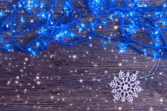 Garland with blue lights and a white snowflake on a wooden background. Christmas and New Year background. Garland with blue lights and a white snowflake on a royalty free stock images