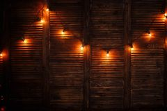 Garland Christmas lights lit on the wooden brown. Wall stock images