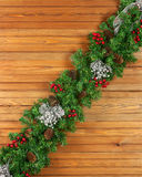 Garland with Christmas ornaments and pine cones on wooden backgr Stock Photo
