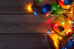 Garland and Christmas tree branches on wooden tab Royalty Free Stock Photos