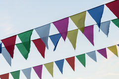 Garland of colorful flags of triangular shape, pennants against blue sky. City street holiday. Modern background, banner. Garland of colorful flags of triangular Stock Photos