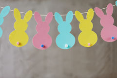 Garland with colorful paper rabbits on gray background. Concept Easter Bunny Banner Royalty Free Stock Photo