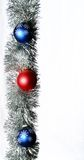 Garland And Glass Balls. Silver garland decorated with three glass Christmas balls with copy space Stock Photo