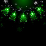 Garland of green fir trees. Electric garland of green lights in the form of  fir on a black background with snowflakes Royalty Free Stock Images