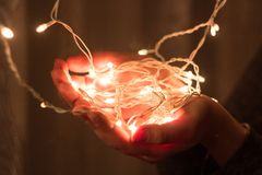 The garland in hands. Bright white garland in hands. Christmas miracles and joy Stock Image
