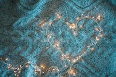 Garland heart with glowing lights in the background of a fluffy grey blanket royalty free stock photography