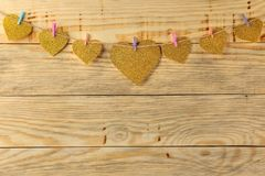 A garland of hearts on clothespins on a natural wooden background. view from above . space for text stock photography