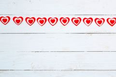 Garland of hearts on a wooden background. Valentine`s Day royalty free stock photos