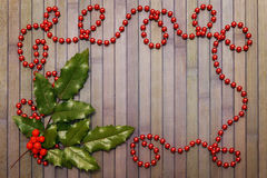 Garland and holly leaves Royalty Free Stock Images