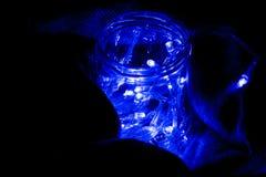 Garland in a jar in a rug. Glowing light bulb garland Stock Photo