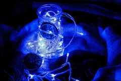 Garland in a jar in a rug. Glowing light bulb garland Royalty Free Stock Photos