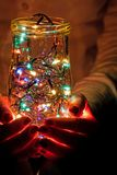 Garland in a jar in a rug. Glowing light bulb garland in the hands Stock Image
