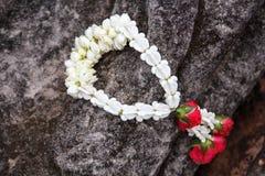 Garland of jasmine flower on hand of Buddha Stock Images